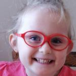 Uśmiechnięta dziewczynka w czerwonych okularach